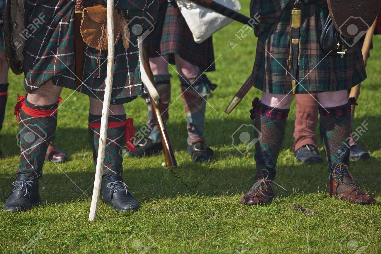 legs of medieval scottish warriors wearing tartan kilts selective