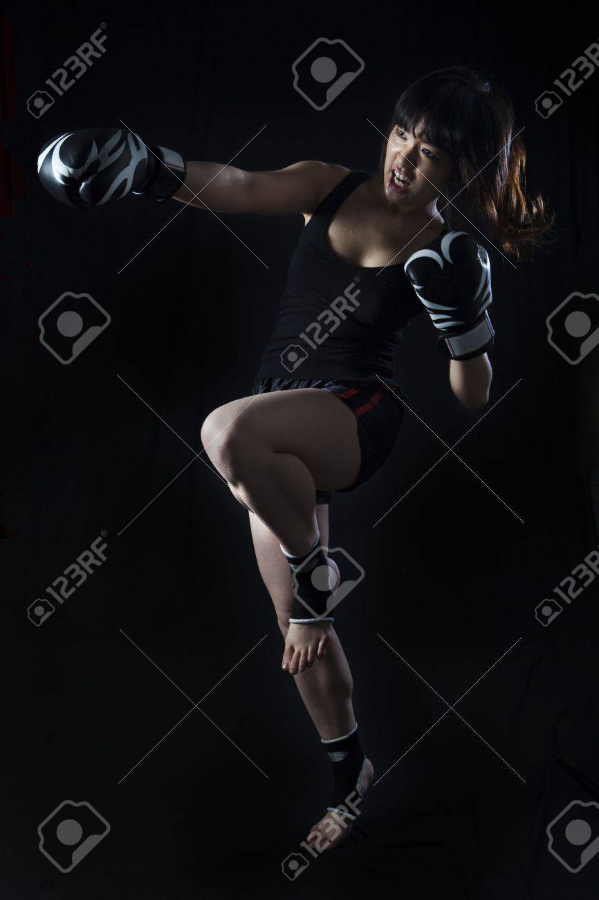 Young Asian Woman Muay Thai fighter in defensive position  On black background Stock Photo - 15905266