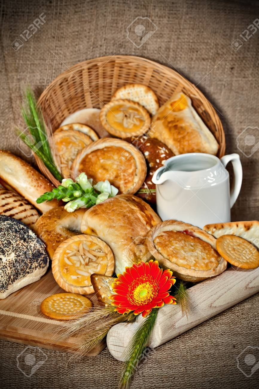 Various baked goods with a cutting board, wooden utensil and cereal ears Stock Photo - 17245368
