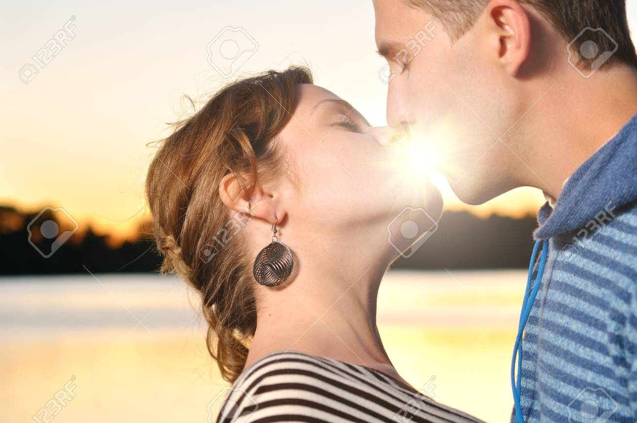 young attractive couple is kissing at sunset Stock Photo - 8407504