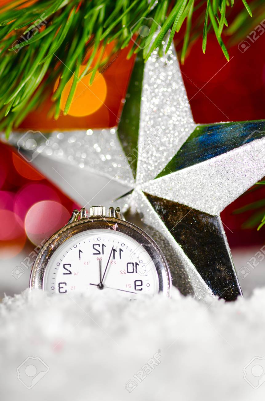 decorative star and clock on snow with christmas tree branch on blurred background Stock Photo - 13642288