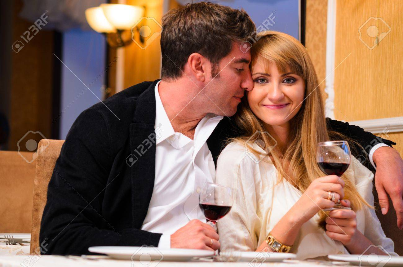 laughing embracing couple is sitting at restaurant and drinking wine Stock Photo - 19671843