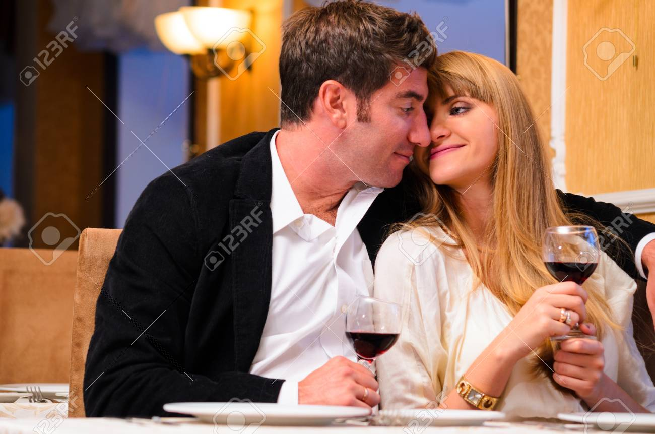 laughing embracing couple is sitting at restaurant and drinking wine Stock Photo - 19729713