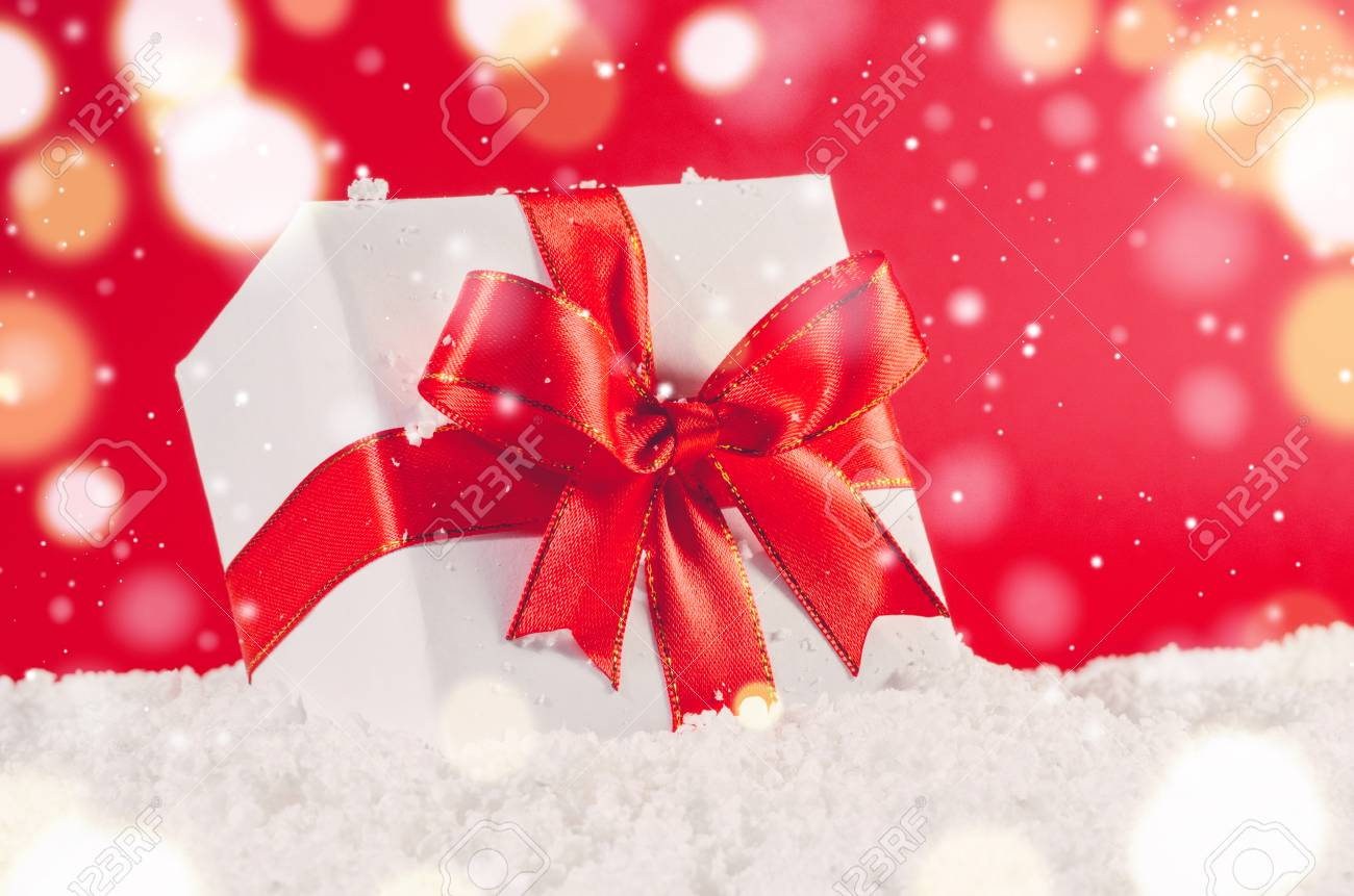 stock photo white decorative christmas gift box with ribbon on snow against red festive background