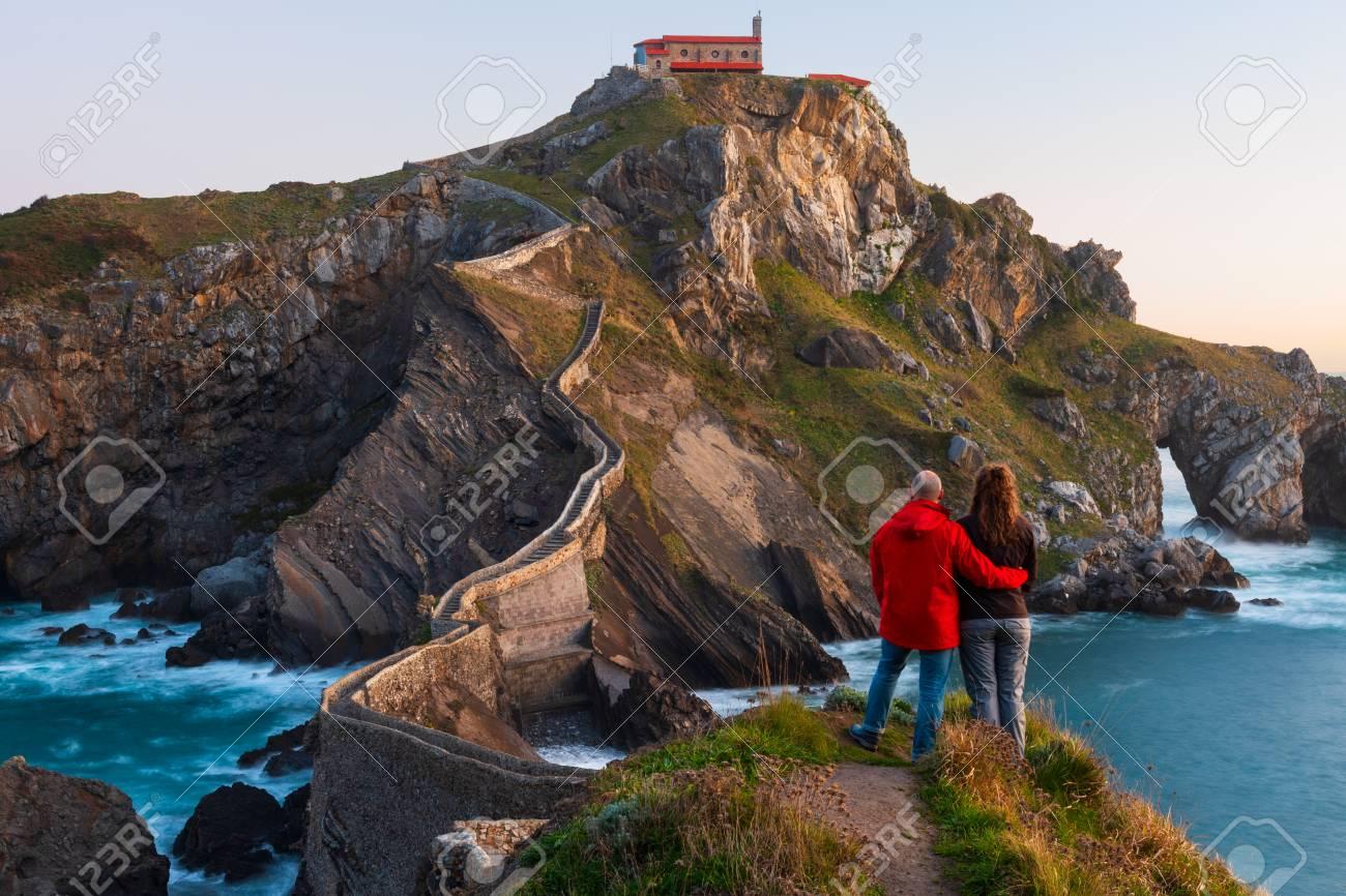Couple against San Juan de Gaztelugatxe, its medieval stairs and bridge at sunrise, Basque Country, Spain - 121171335