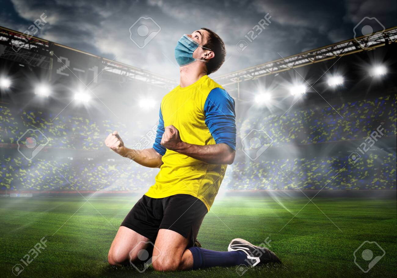 Soccer or football player wearing mask. Team sports player in medical mask emotionally kneel on stadium during coronavirus outbreak. - 149664051