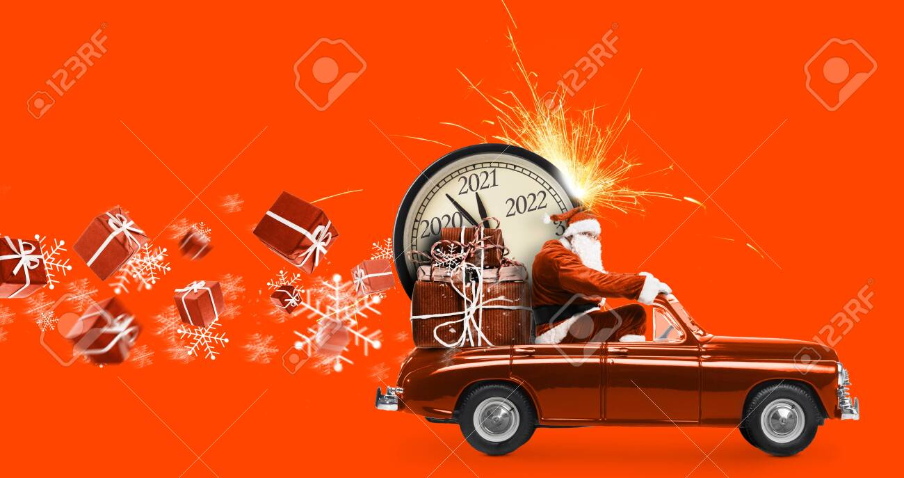 Christmas is coming. Santa Claus on toy car delivering New Year 2021 gifts and countdown clock at orange background with fireworks - 153141454