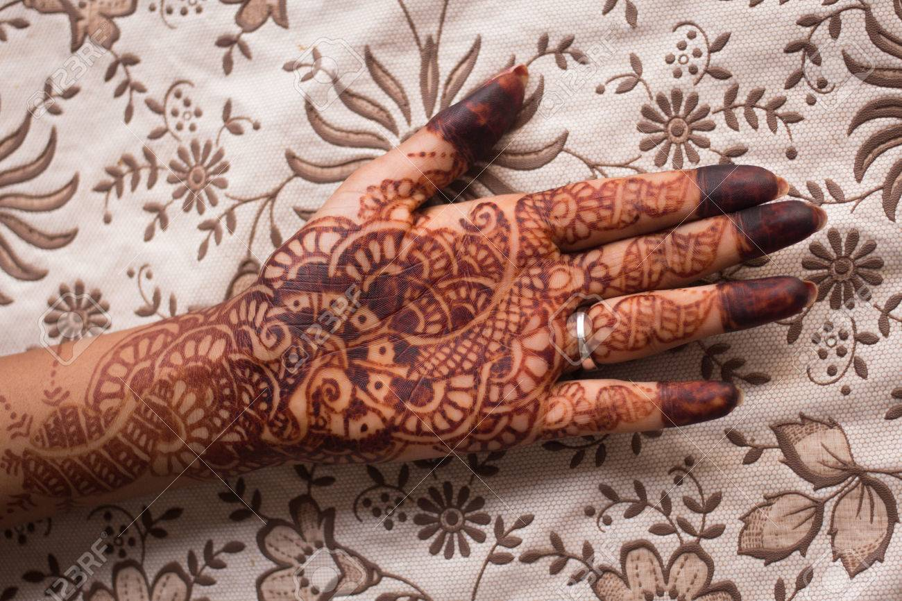 Indian Mehndi Henna Painting In Womans Hand At Flowery Background