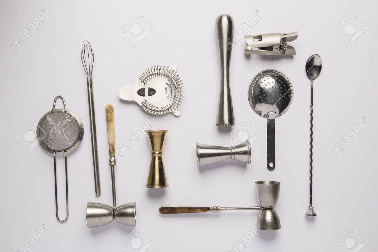 Flat lay composition with bartender iron tools, such as cocktail shaker, jigger, mixing glass, stirring spoon. Background is white. - 143017466