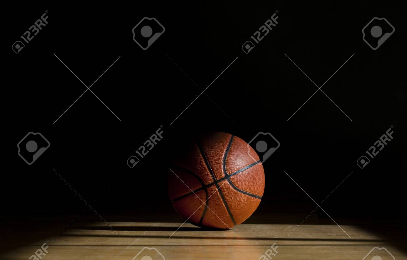 Basketball ball on the parquet with black background - 120614457