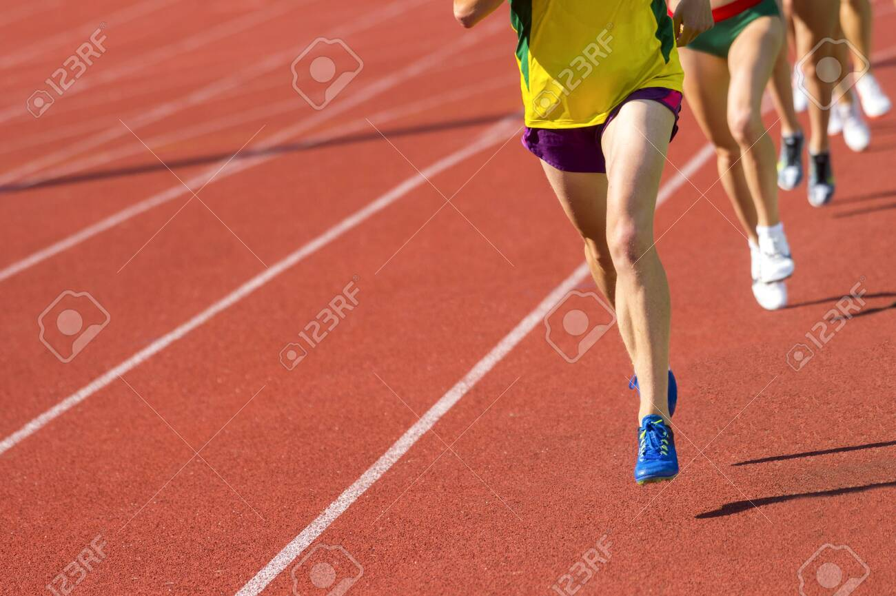 Athletics people running on the track field. Sunny day - 124625007