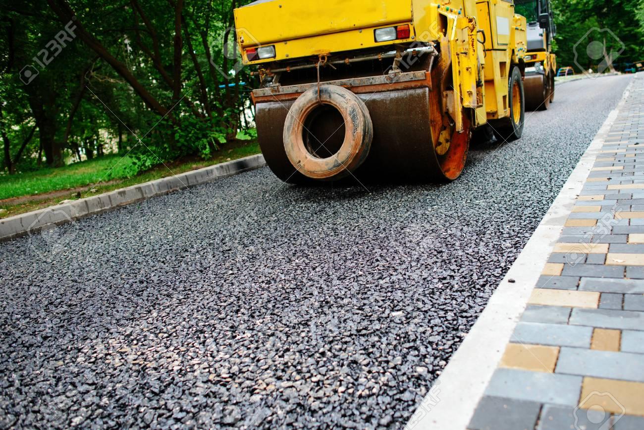 Carrying out repair works: asphalt roller stacking and pressing hot lay of asphalt. Machine repairing road. - 85040870