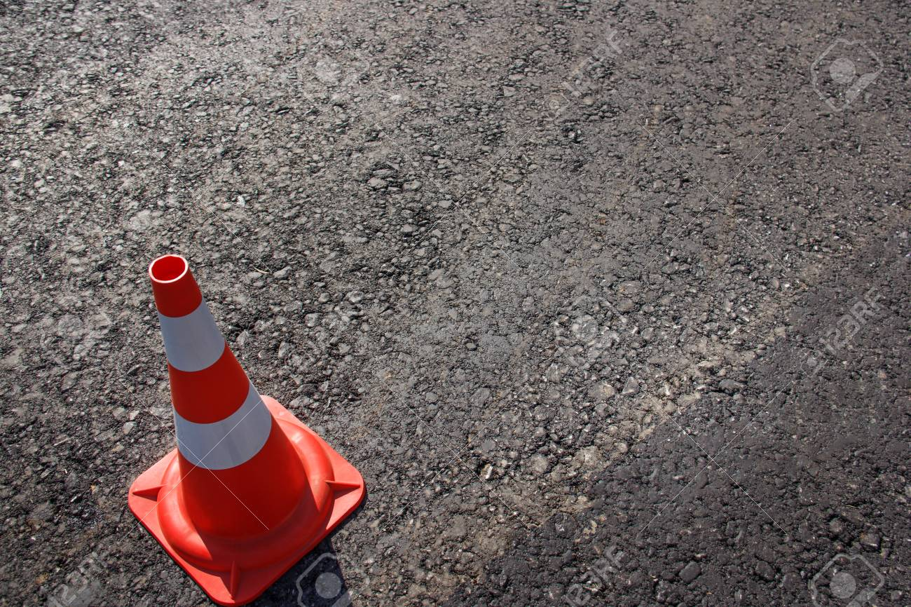 traffic cone, with white and orange stripes on gray asphalt, copy space. - 118032722