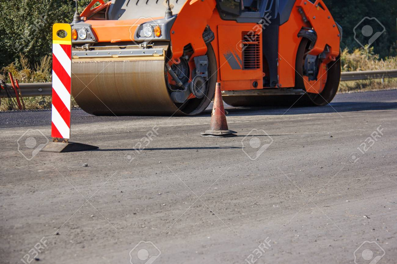 Carrying out repair works: asphalt roller stacking and pressing hot lay of asphalt. Machine repairing road. - 118032723