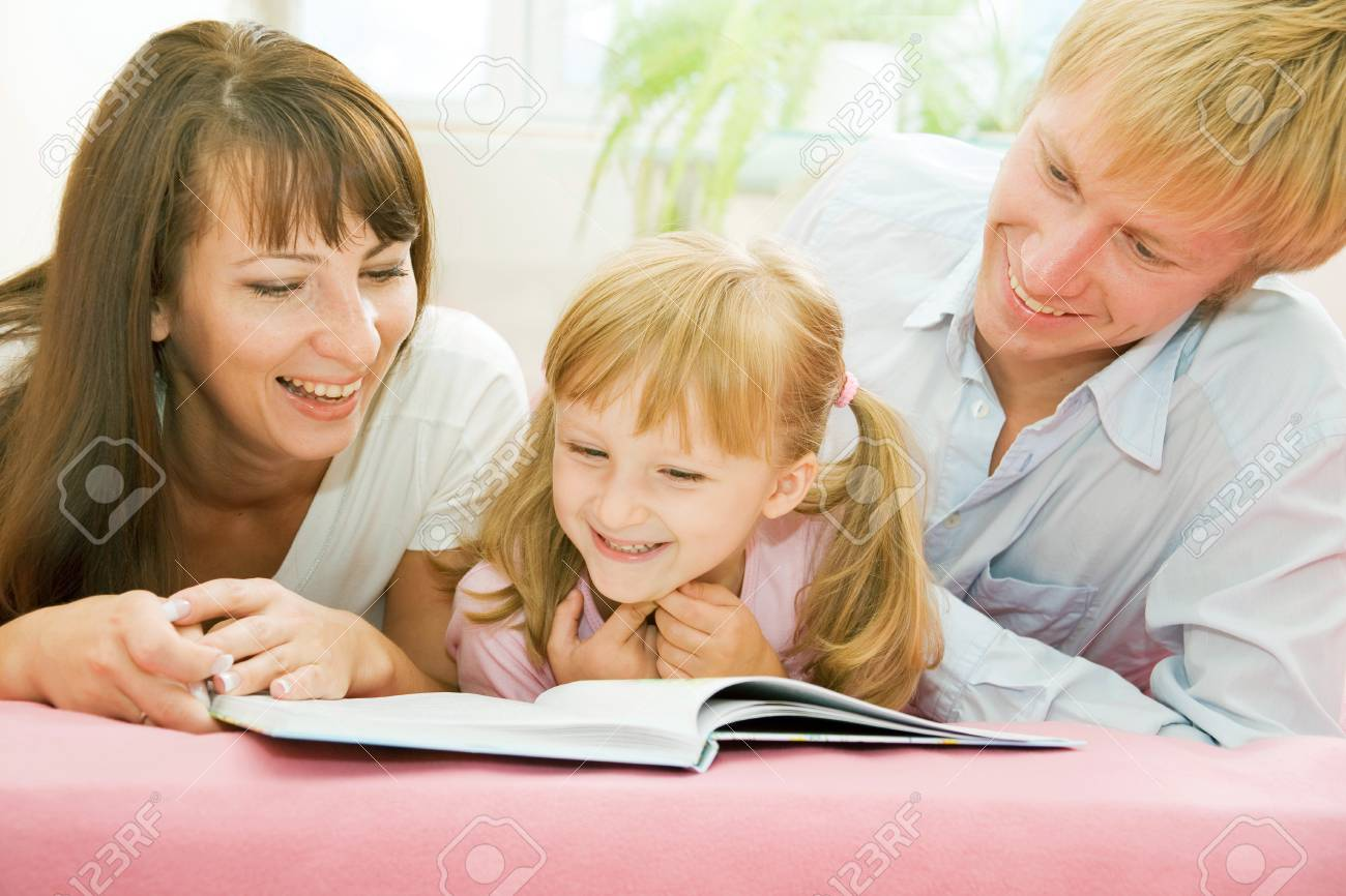 Portrait of happy family reading the book together at home Stock Photo - 4143288