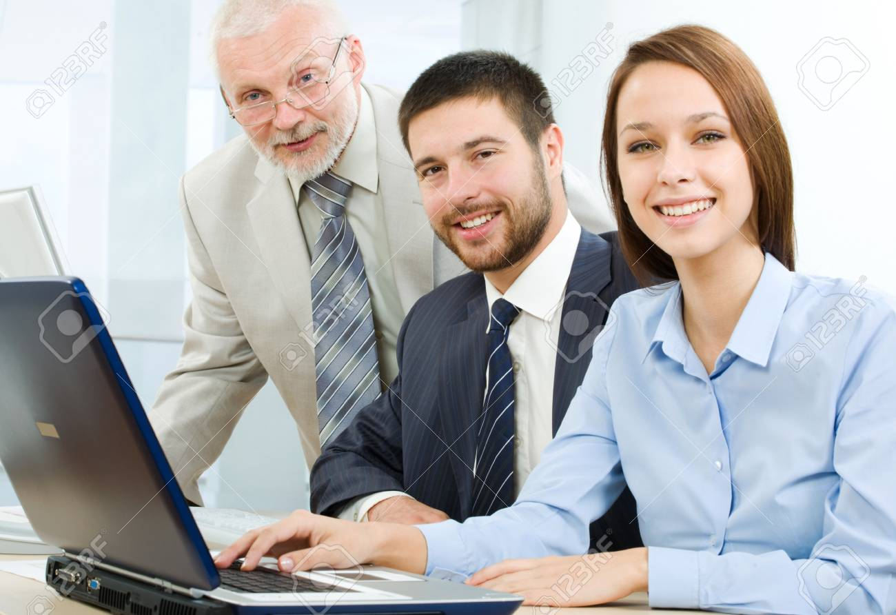 A group of business people sitting at table, looking at camera Stock Photo - 9265154