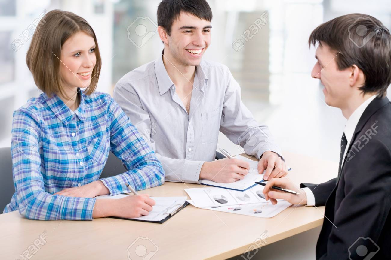 Manager talks to a young couple in the bank Stock Photo - 14735139