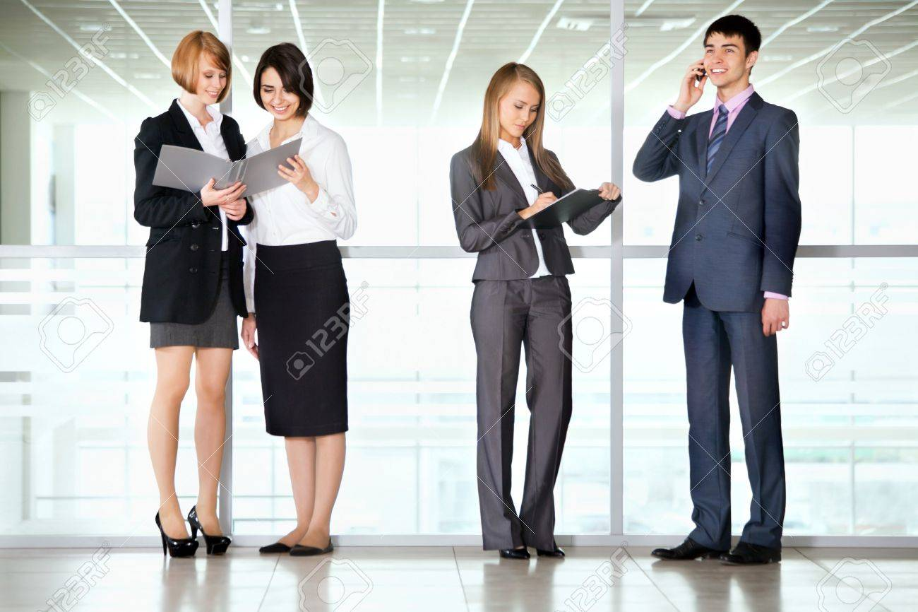 Full length portrait of professional business people discussing reports in a office corridor - 16120698