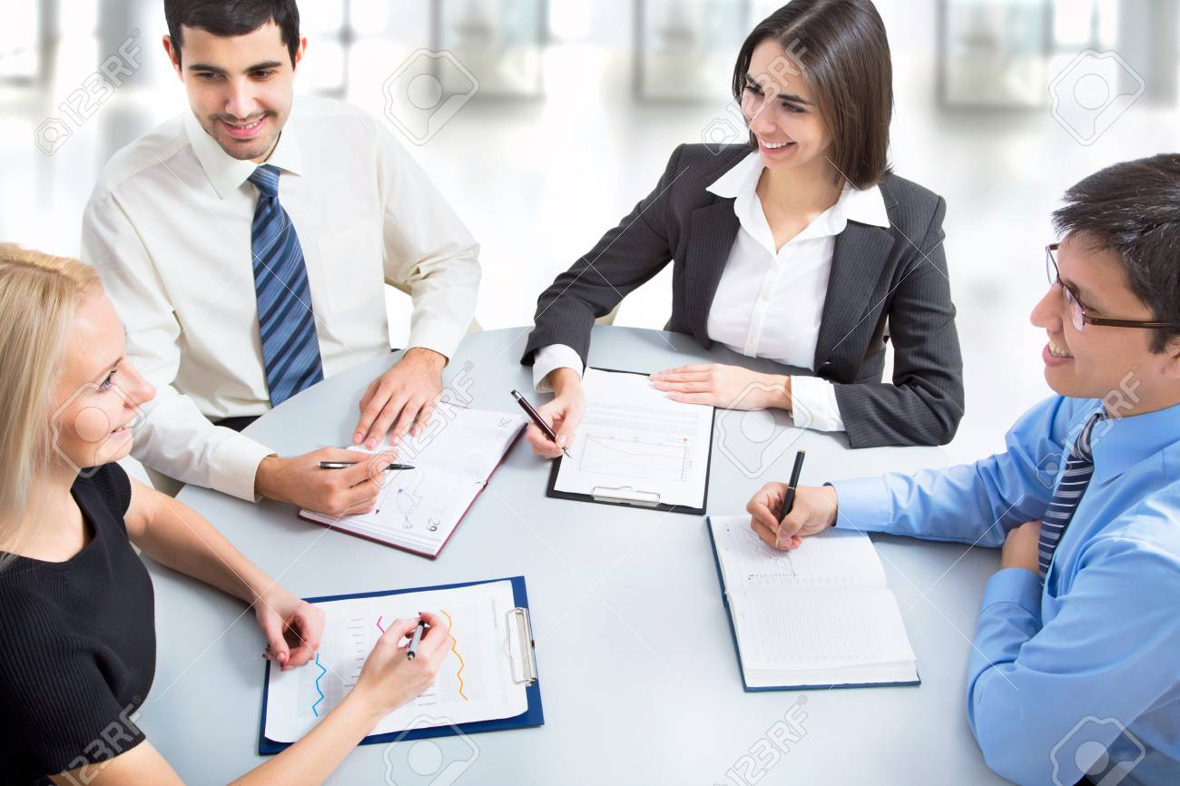 A business team of four plan work in office Stock Photo - 21258389
