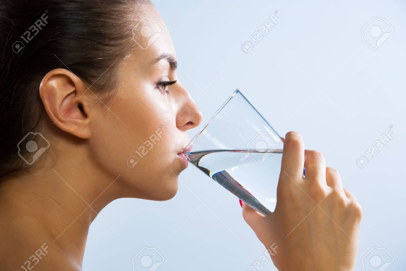 Close-up of pretty young woman drinking water from glass - 60685207