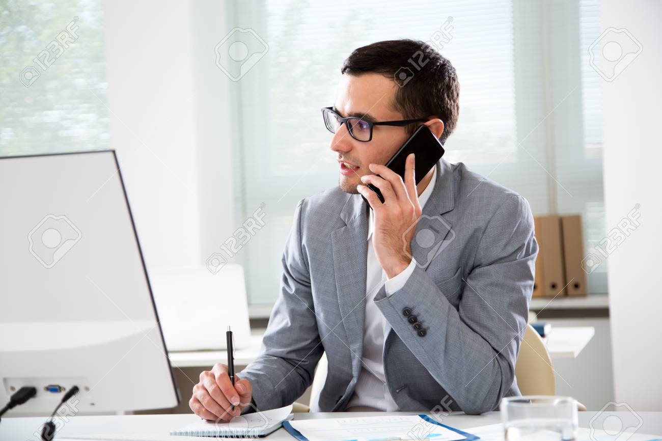 Young handsome businessmantalking on the phone in an office - 116694936