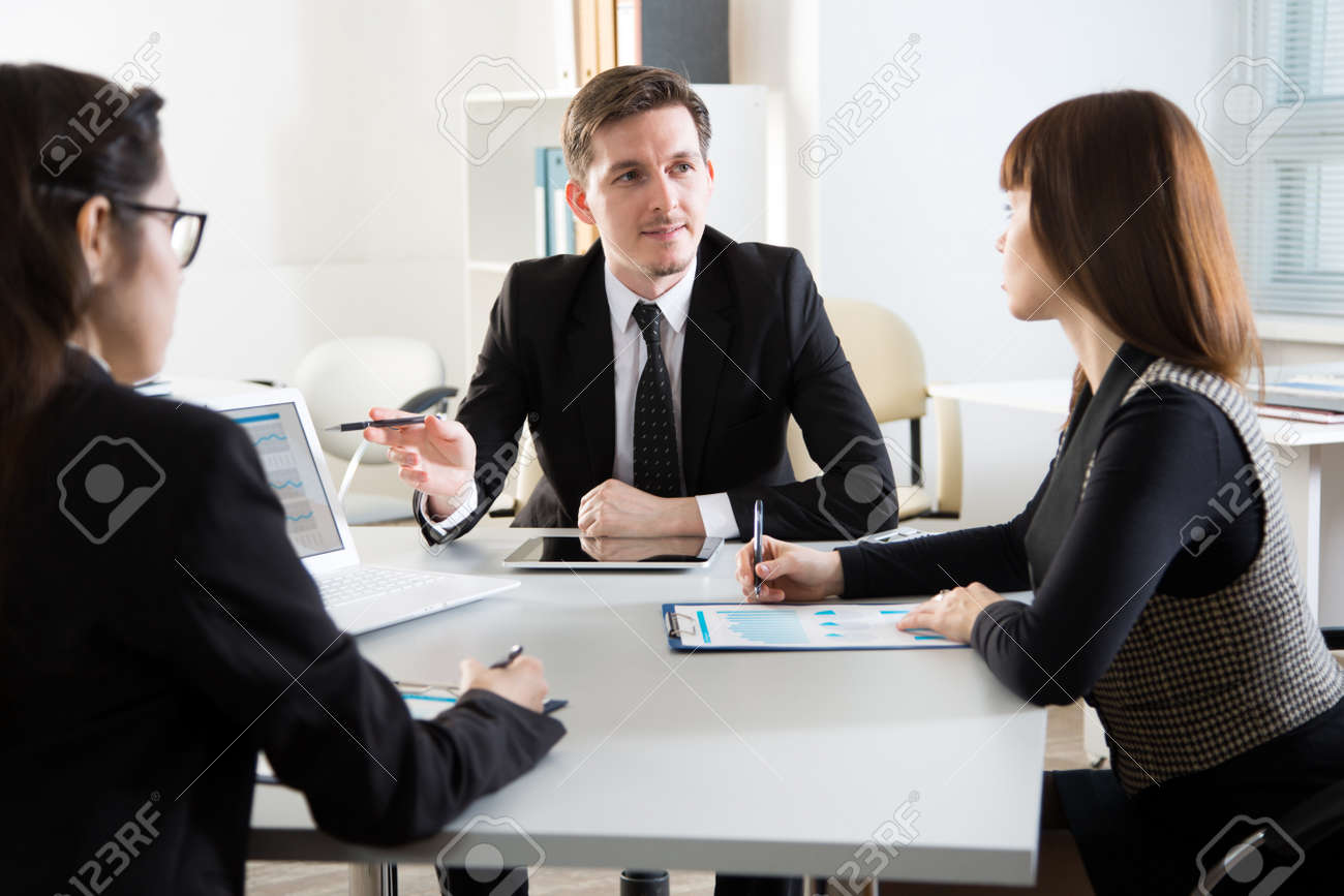 Businesspeople discuss a new project in the office - 120595393