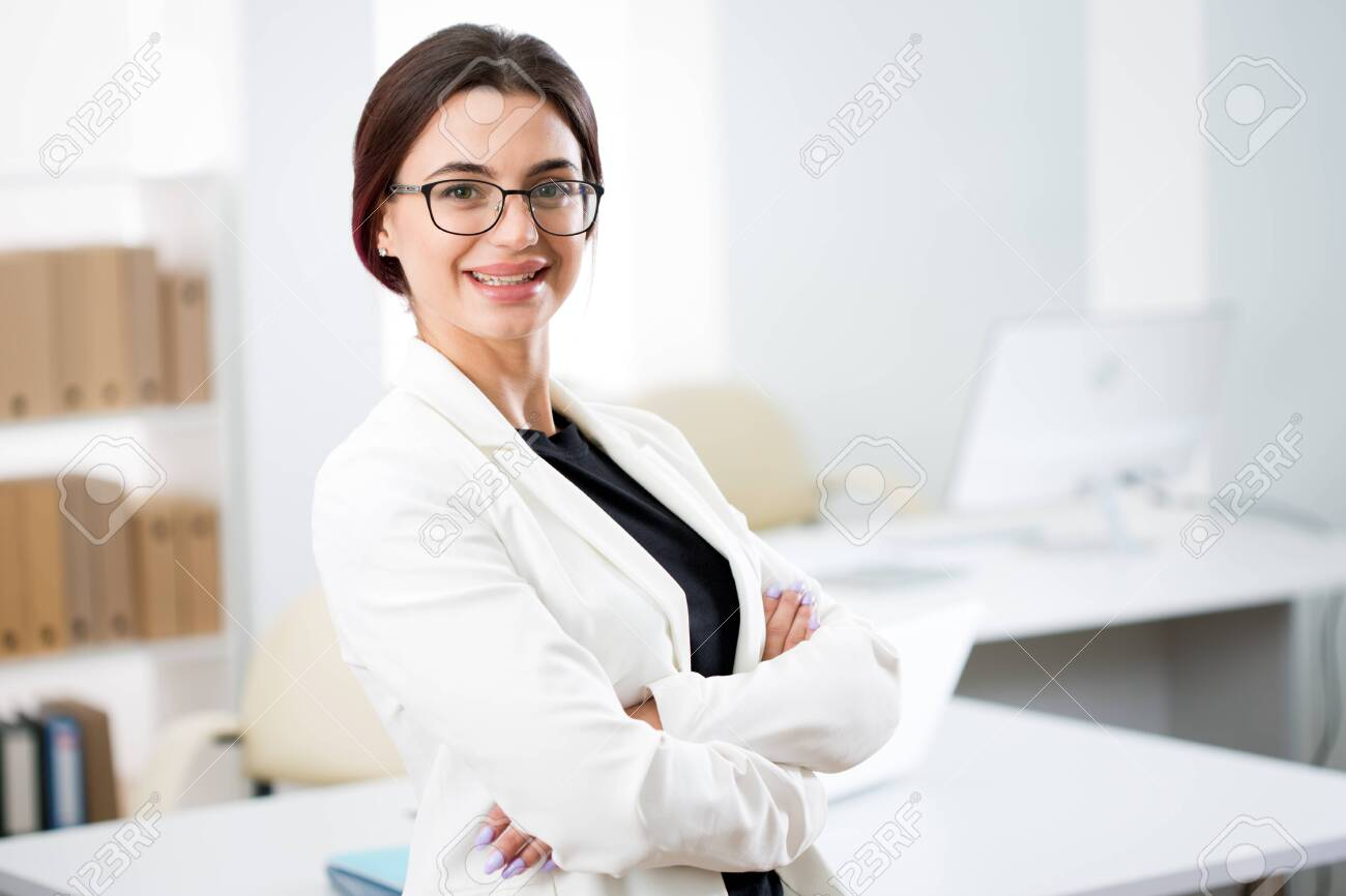 Portrait of a smiling young attractive business woman in an office - 122504659