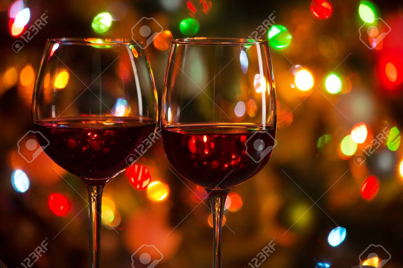 Crystal glasses of wine on the background of Christmas lights - 133230305