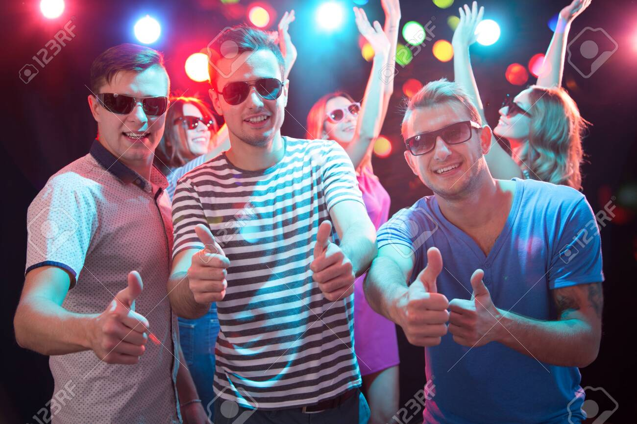 Happy young friends showing OK sign in the night club - 133843831