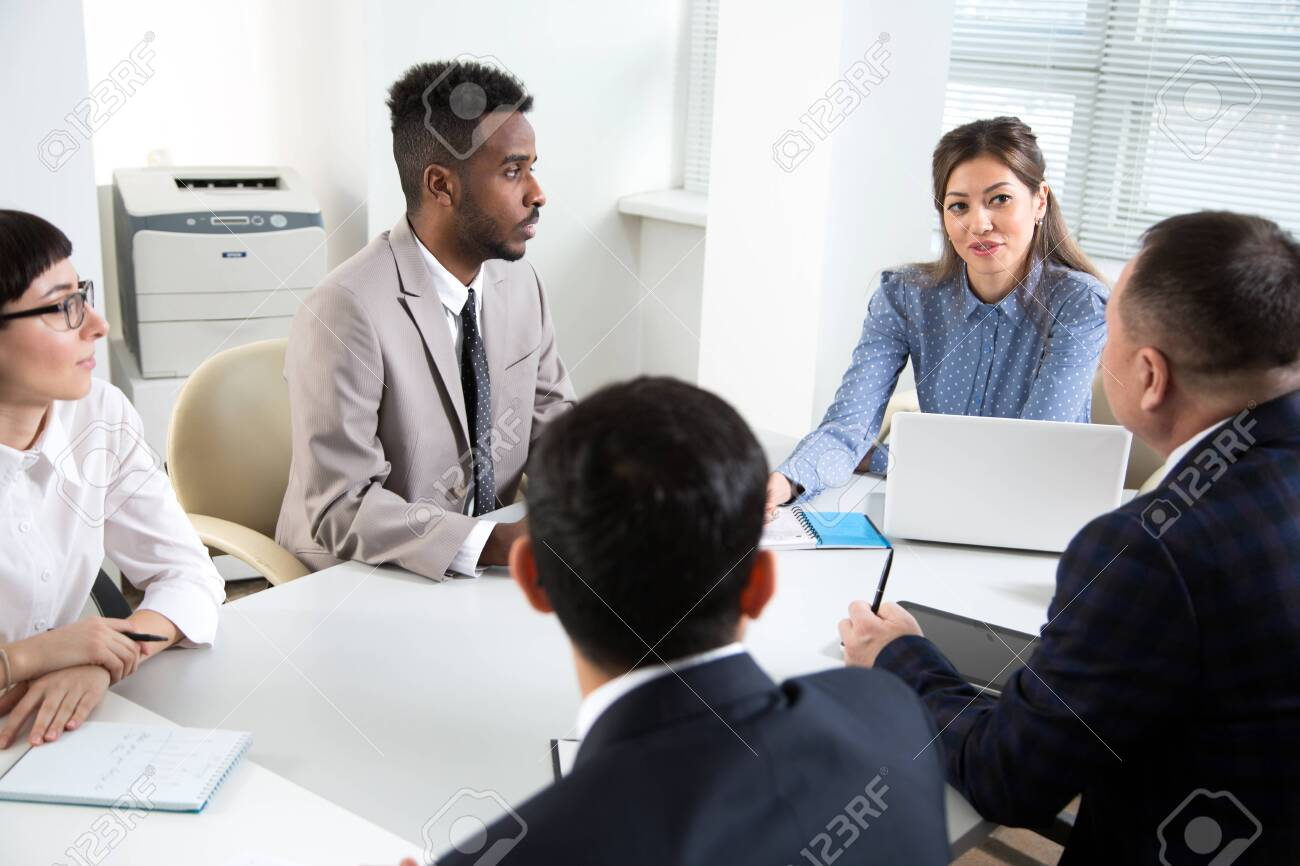 Multy-ethnic group of young business people sitting at the office desk and working with computer - 139479225