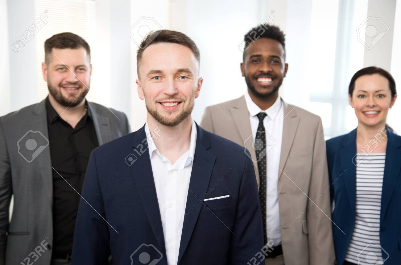 Portrait of successful businessman and his colleagues on the background at the office - 144050501