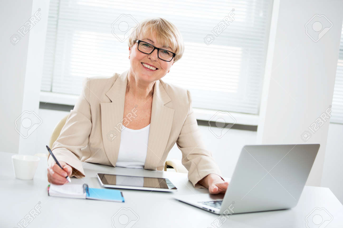 Portrait of mature business woman looking at camera at workplace in an office - 150179101