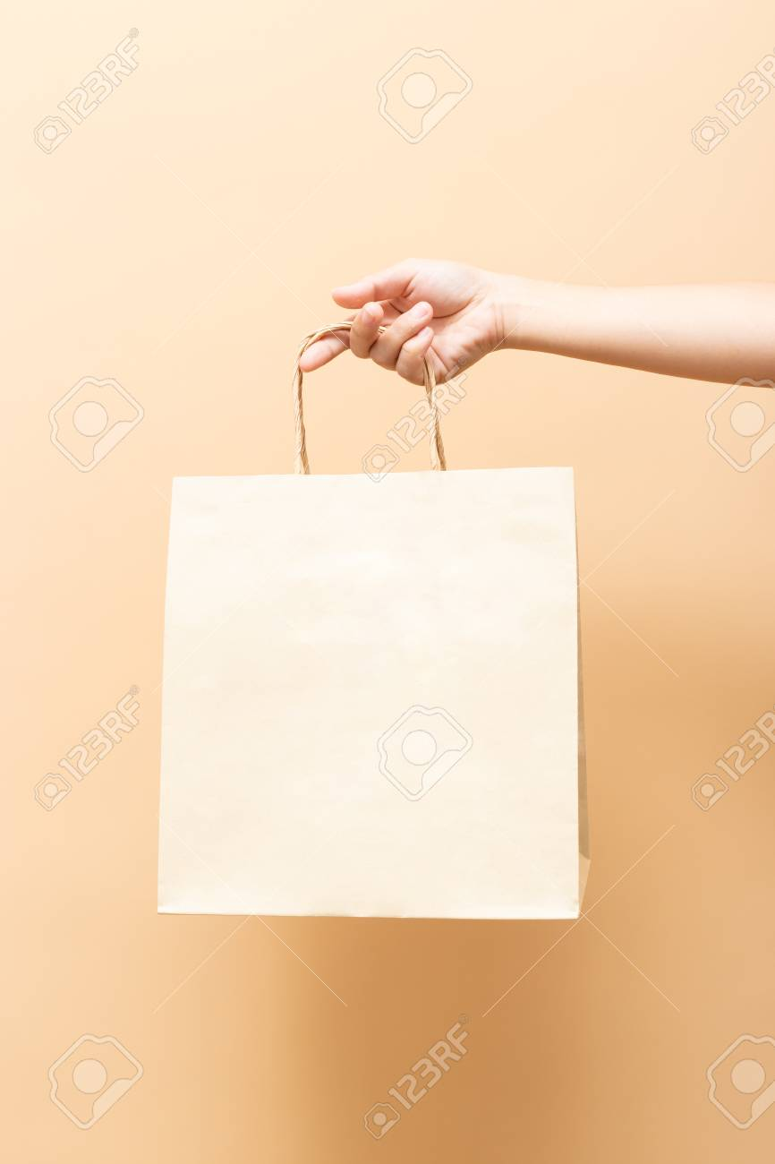 Hand holding a paper bag isolated - 117411827