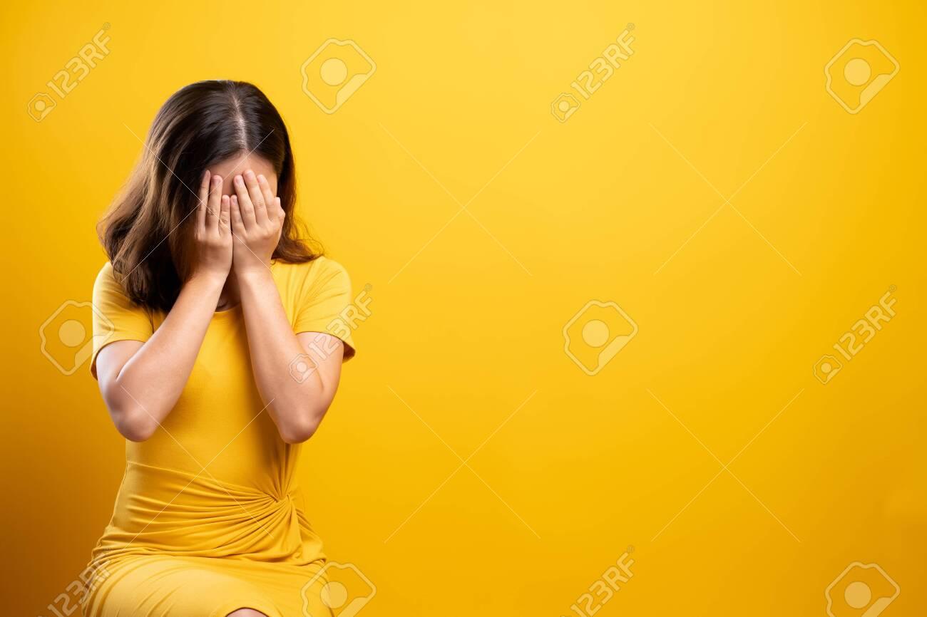 Sad woman isolated over yellow background - 119884167