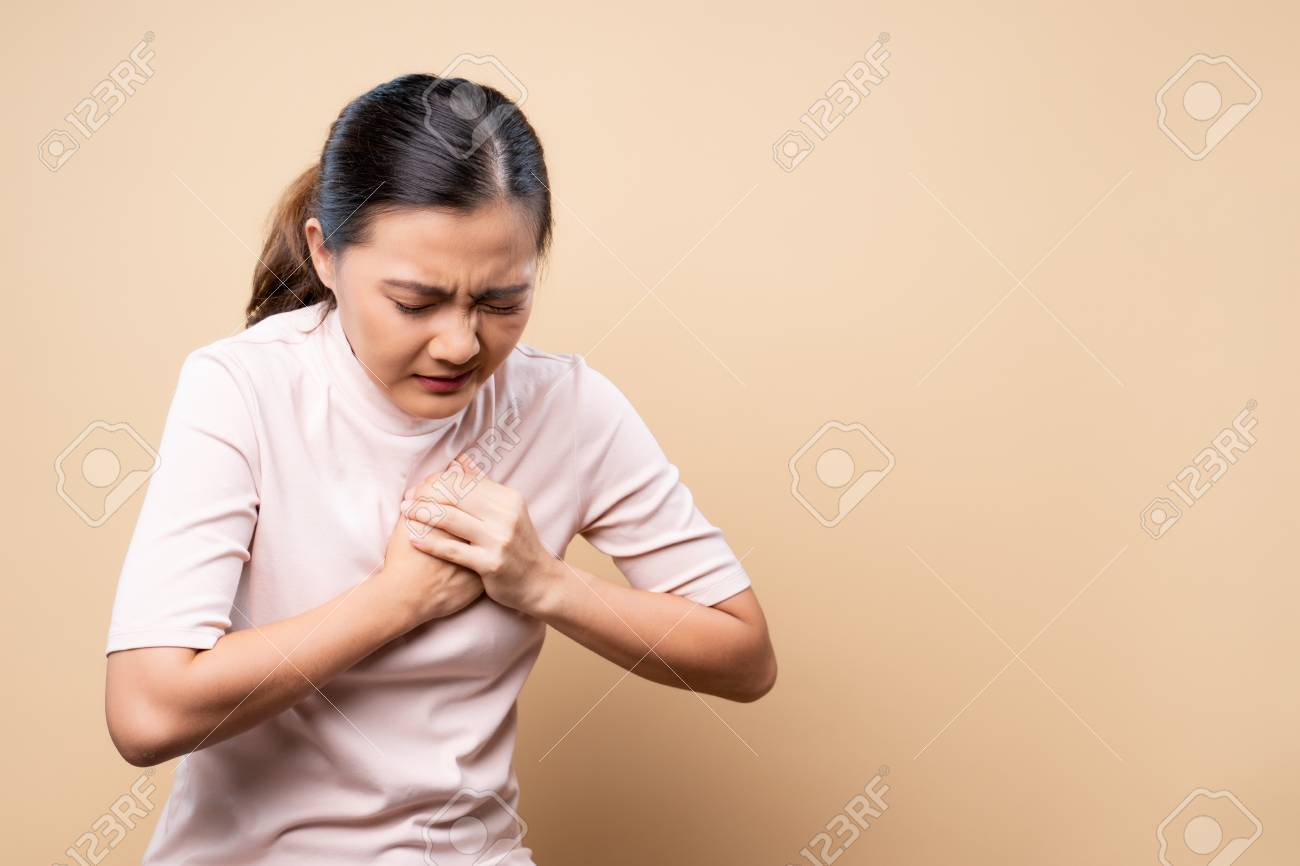 Woman has chest pain isolated over beige brown - 120220956