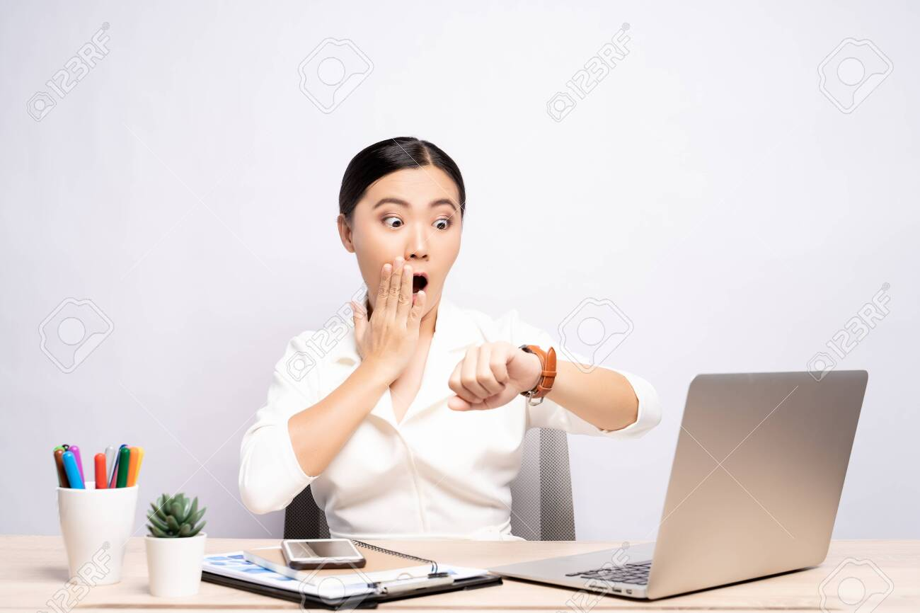 Shocked woman holding hand with wrist watch at office isolated over background - 126021941