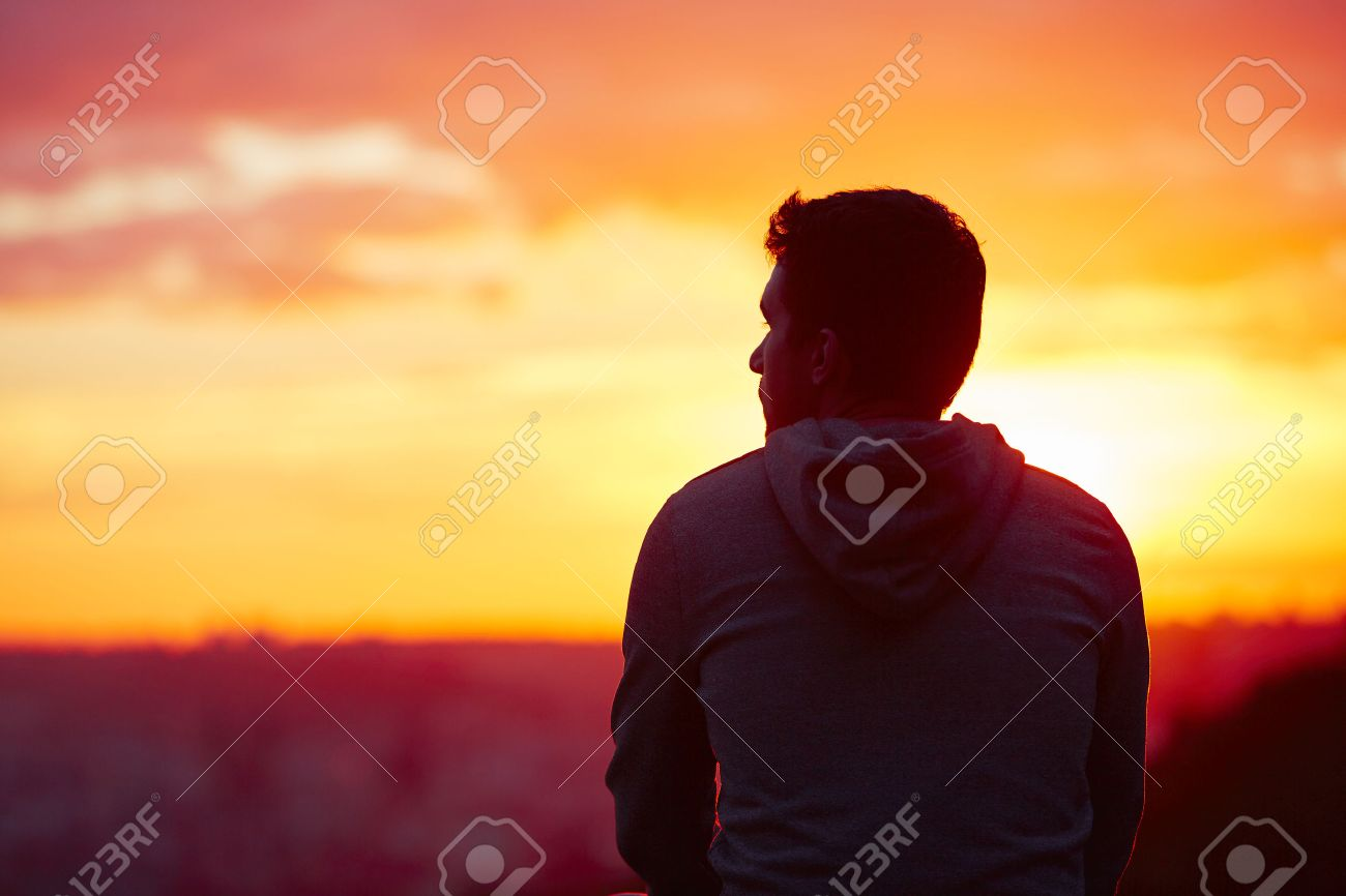 Young man is looking at the sunrise. Standard-Bild - 45778974