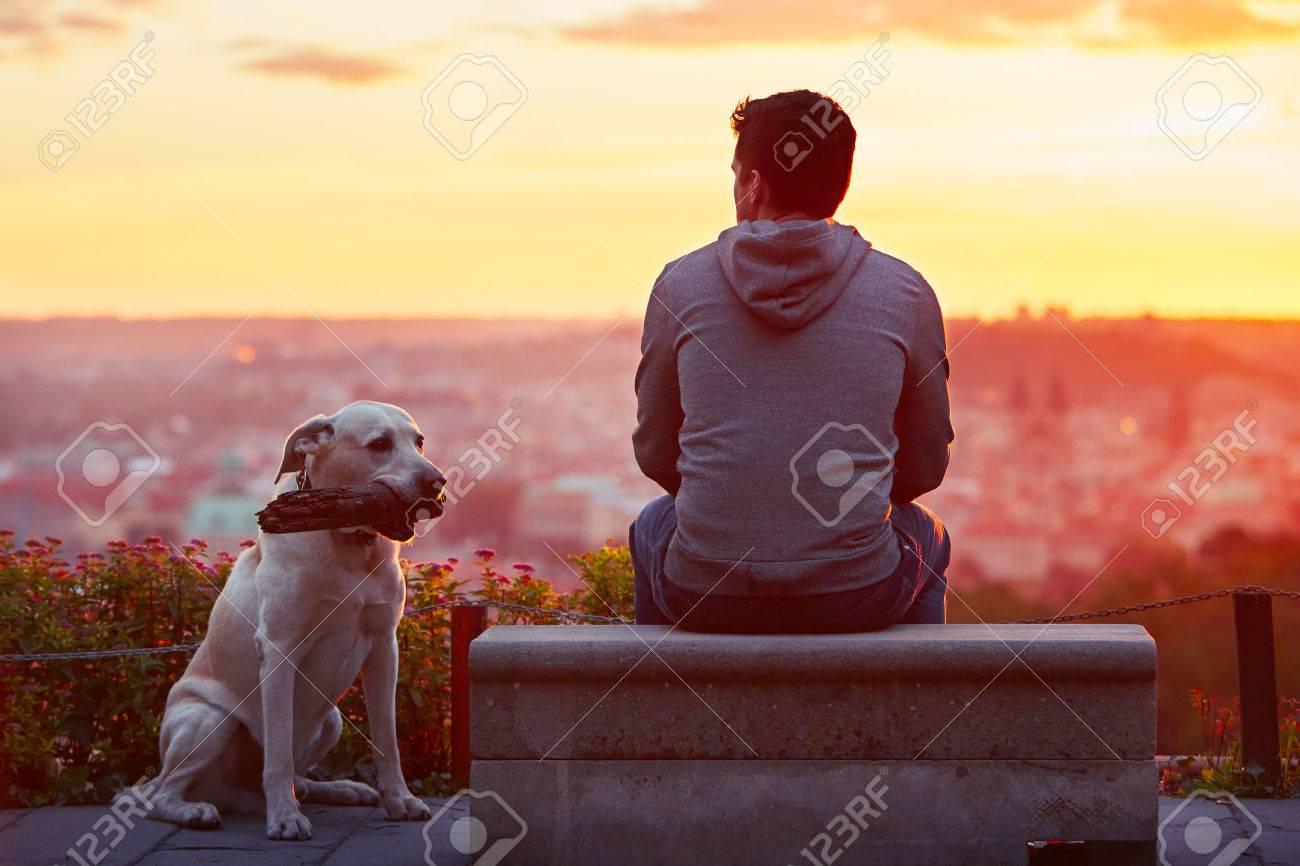 Young man with his dog at the sunrise. Standard-Bild - 45779079