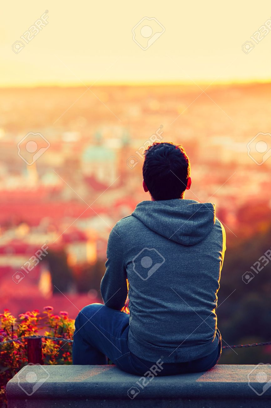 Young man is looking at the sunrise. Standard-Bild - 45779083