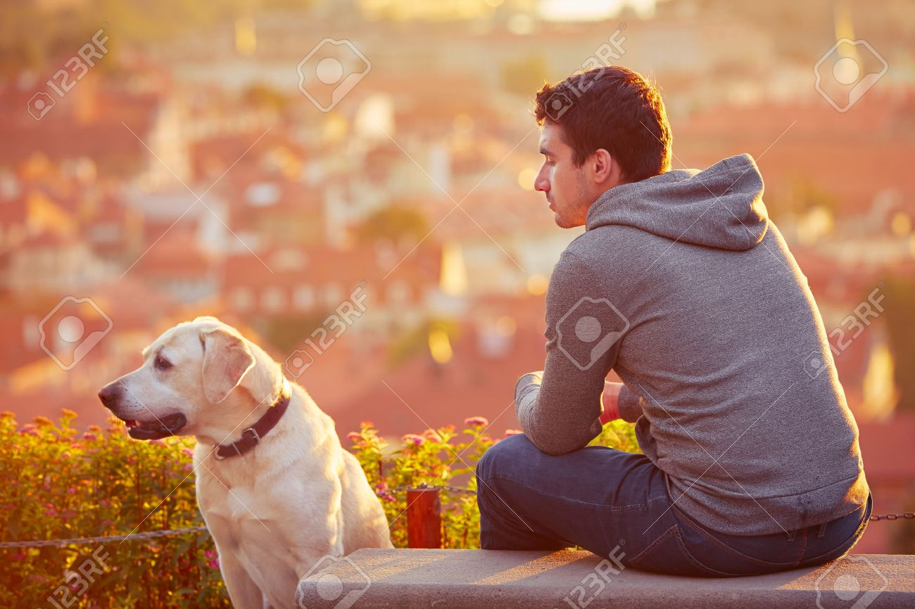 Young man with his dog at the sunrise. Standard-Bild - 45779087