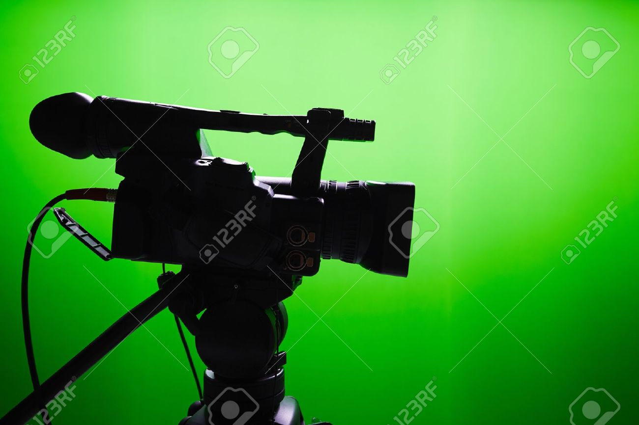 Silhouette of digital video camera in front of the green screen Standard-Bild - 47464279