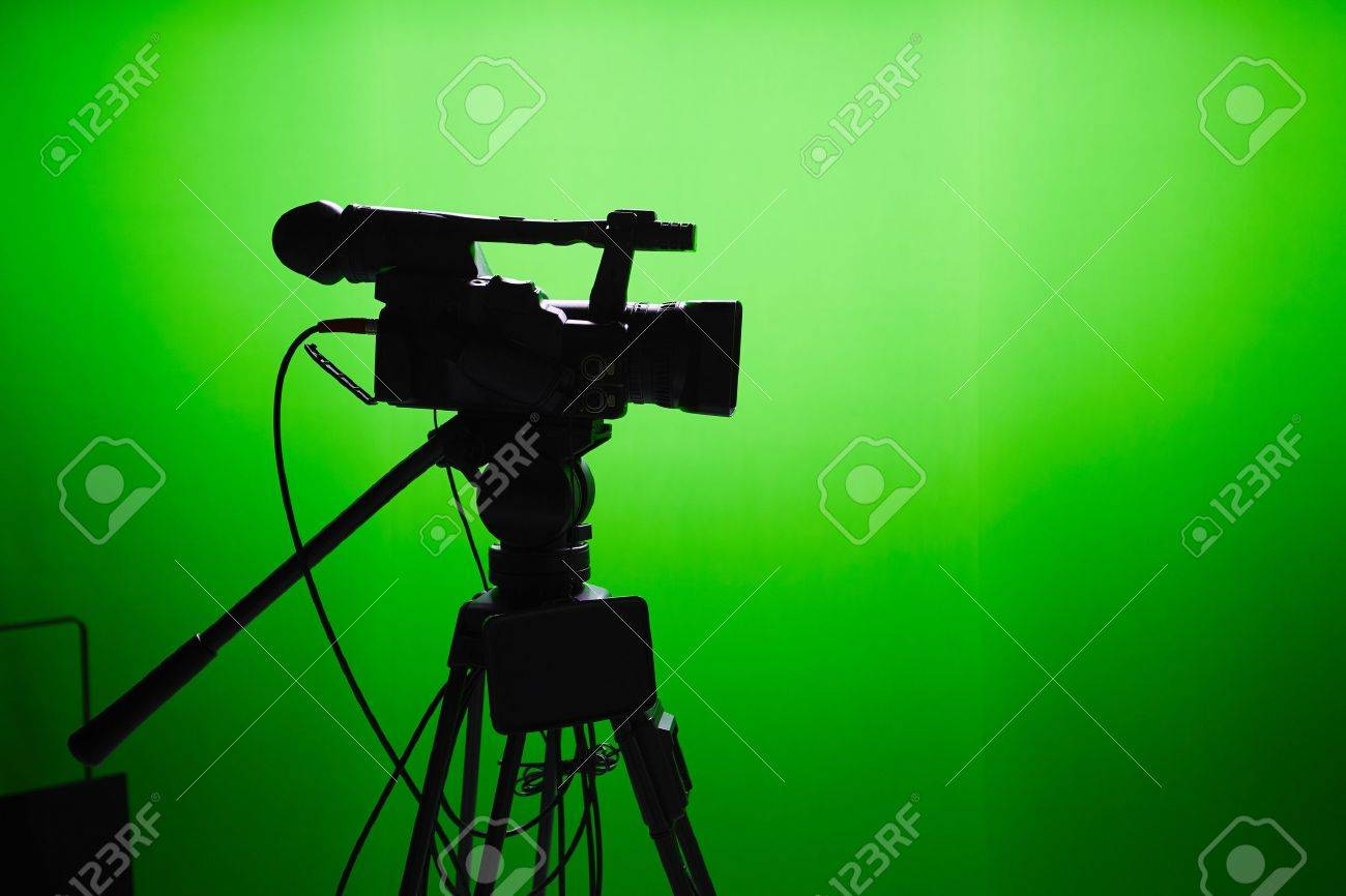 Silhouette of digital video camera in front of the green screen Standard-Bild - 47464280