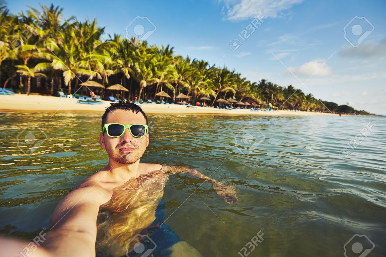 Young man on vacation taking selfie in the sea. Standard-Bild - 50765742