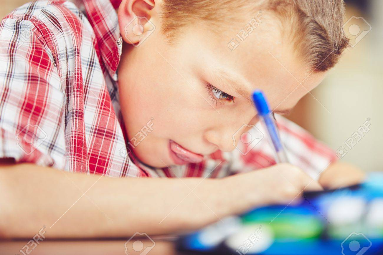 Little boy is doing his homework for elementary school. - 54025500