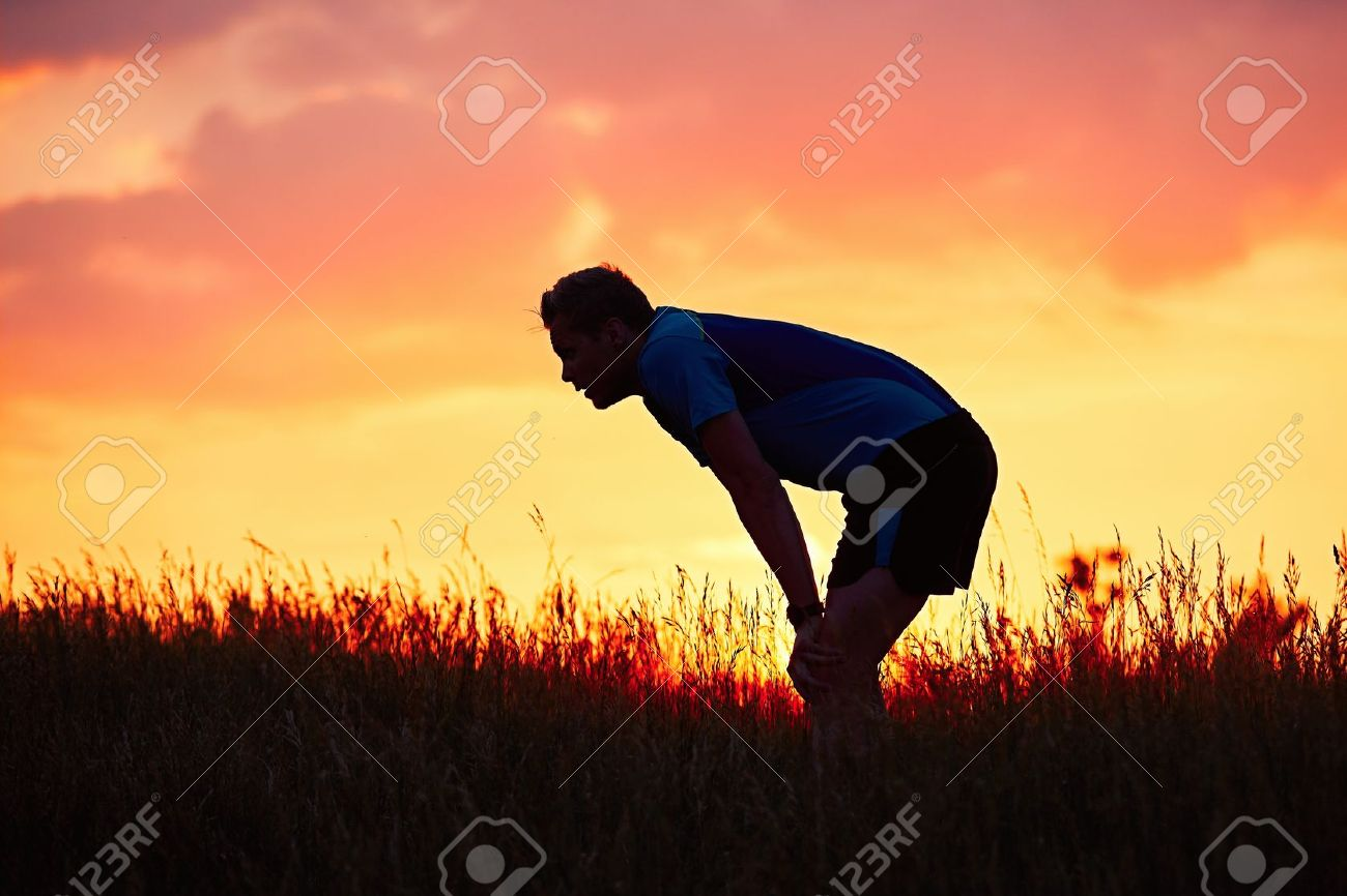 Silhouette of runner. Outdoor cross-country running. Pensive young man is taking rest after running in the nature during golden sunset. Standard-Bild - 58733824