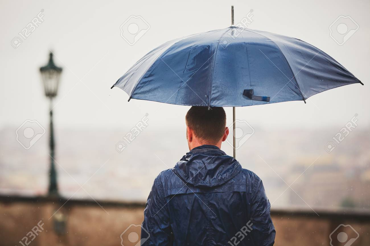 e373d4c20cc25 Rainy Day. Young Man Is Holding Blue Umbrella And Walking In.. Stock ...