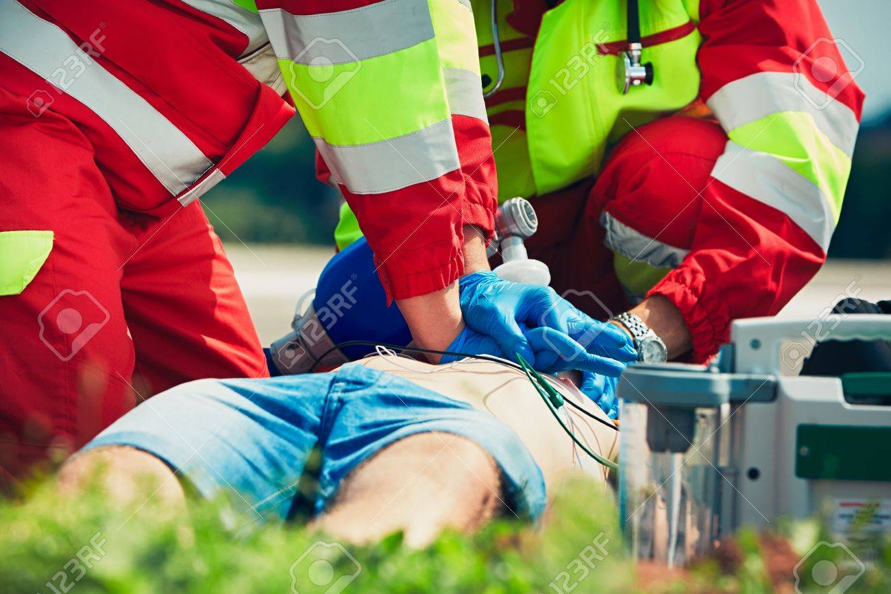 Cardiopulmonary resuscitation. Rescue team (doctor and a paramedic) resuscitating the man on the street. - 60418006