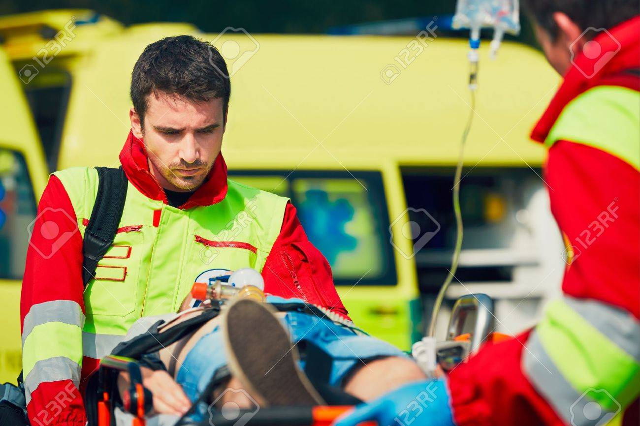 Team of rescuers (paramedic and doctor) preparing the patient after resuscitation for transport to the hospital. - 60418017