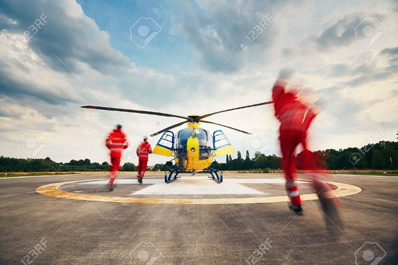 Alarm for the air rescue service. Team of rescuers (paramedic, doctor and pilot) running to the helicopter on the heliport. - 60863543