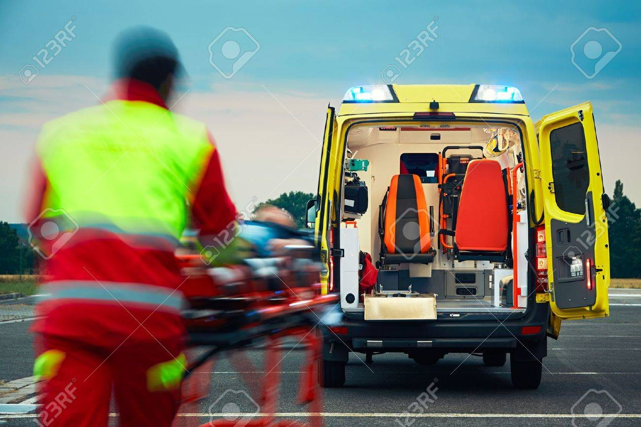 Emergency medical service. Paramedic is pulling stretcher with patient to the ambulance car. Standard-Bild - 60418020